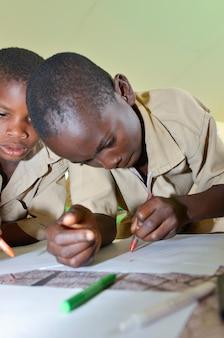 Costa de abidjan / marfim - 1 de dezembro de 2015: um estudante ivoirien de 8 anos de idade desenhando em papel branco.
