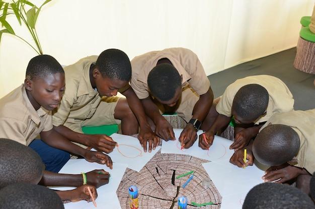 Costa de abidjan / marfim - 1 de dezembro de 2015: um ivoirien schoolkids de 8 anos de idade desenhando em papel branco.