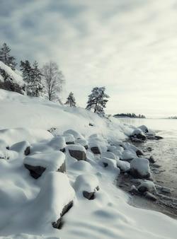 Costa de gelo na água do lago ladoga com neve fresca no inverno