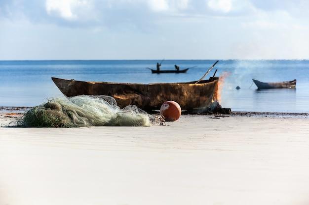 Costa de mombaça o velho barco e instrumentos de pesca na praia com pescadores a bordo