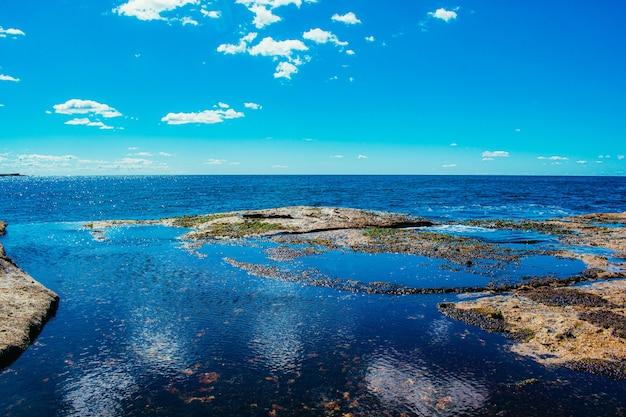 Costa do mar azul fundindo-se com o céu