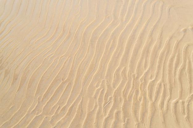 Costa do mar com close-up de areia ondulada. fundo de textura de areia. conceito de verão e férias. vista do topo