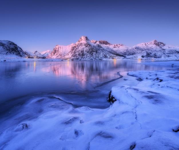 Costa do mar congelada e belas montanhas cobertas de neve no inverno ao entardecer