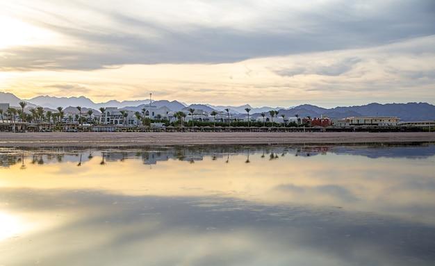 Costa do mar da cidade entre as montanhas. o céu se reflete na água.