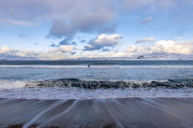 Costa do mar de barents. os surfistas surfam nas ondas geladas