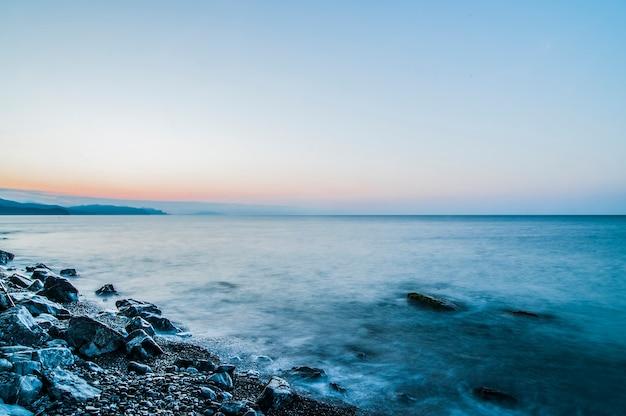 Costa do mar e praia rochosa, céu azul com nuvens brancas