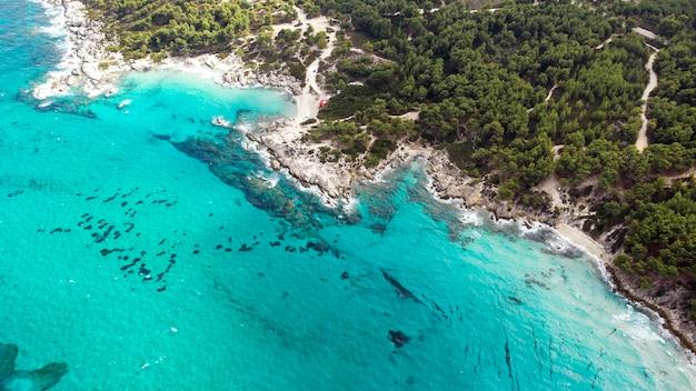 Costa do mar egeu com água azul transparente, vegetação ao redor, pedras, arbustos e árvores, vista do drone, grécia