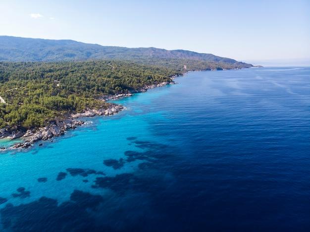 Costa do mar egeu com água azul transparente, vegetação ao redor, vista do drone, grécia