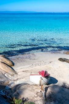 Costa do mar egeu com barco encalhado, rochas na praia, água azul, grécia
