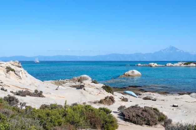 Costa do mar egeu com pessoas que nadam, rochas sobre a água e terra com barco à distância, vegetação em primeiro plano, água azul, grécia