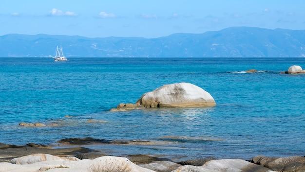 Costa do mar egeu com rochas sobre a água, barco e terra, água azul, grécia