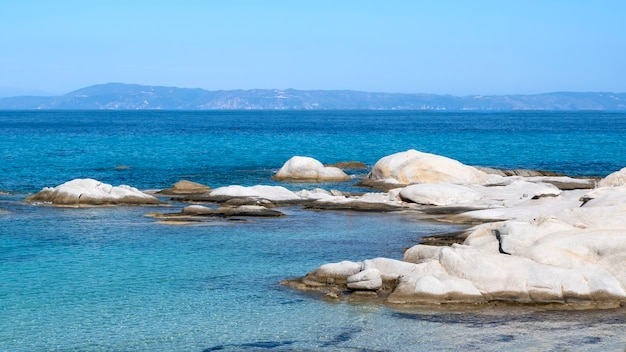 Costa do mar egeu com rochas sobre a água e águas azuis terrestres, grécia