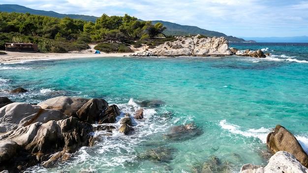 Costa do mar egeu com vegetação ao redor, rochas, arbustos e árvores, água azul com ondas, grécia