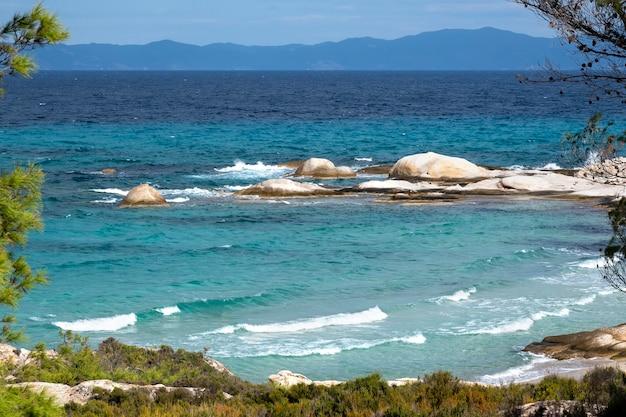 Costa do mar egeu com vegetação ao redor, rochas e árvores, água azul com ondas, grécia