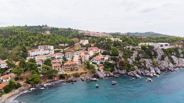 Costa do mar egeu da grécia, edifícios loutra localizados perto das falésias rochosas, vegetação e água azul. vista do drone