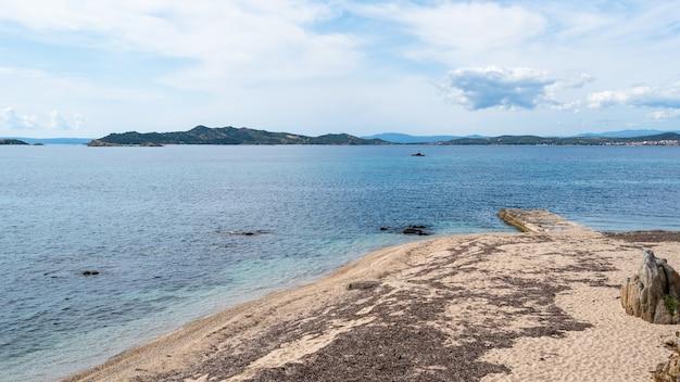 Costa do mar egeu em ouranoupolis com cais antigo e colinas verdes de uma ilha na grécia