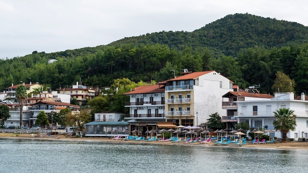 Costa do mar egeu, guarda-sóis e espreguiçadeiras na praia, edifícios na fileira