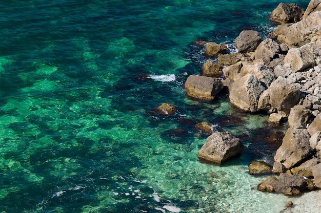 Costa rochosa com água do mar transparente verde-azul
