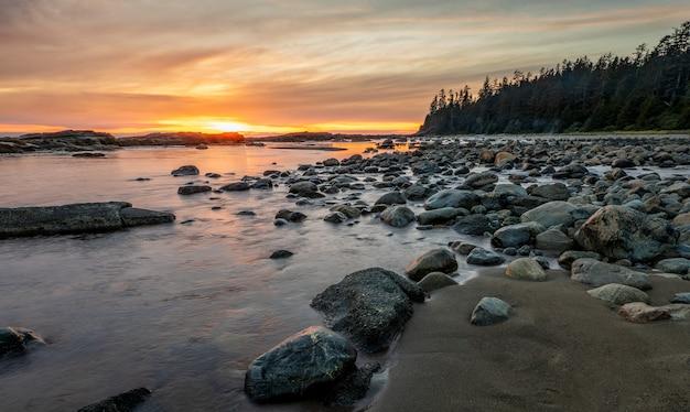 Costa rochosa com pedras na costa durante o pôr do sol