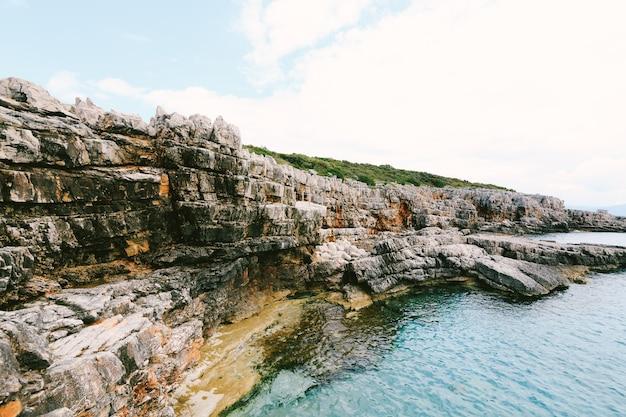 Costa rochosa com textura da superfície da água azul-celeste