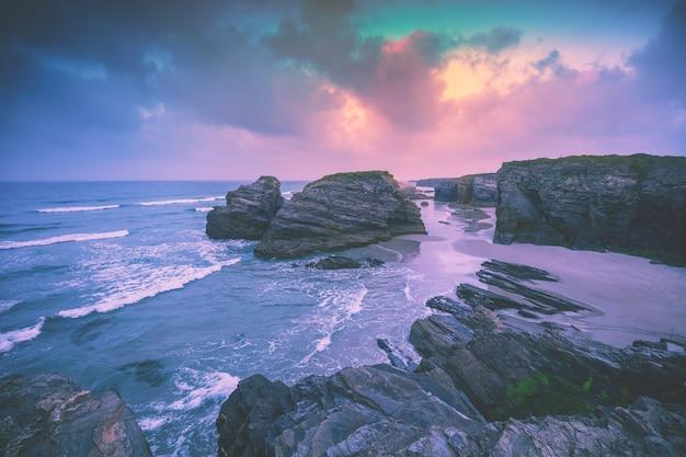 Costa rochosa do mar ao nascer do sol. praia las catedrales na maré baixa. ribadeo, espanha