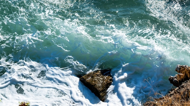 Costa rochosa do mar egeu da grécia, ondas e muita espuma