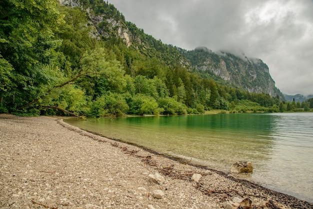 Costa rochosa no lago da montanha na áustria