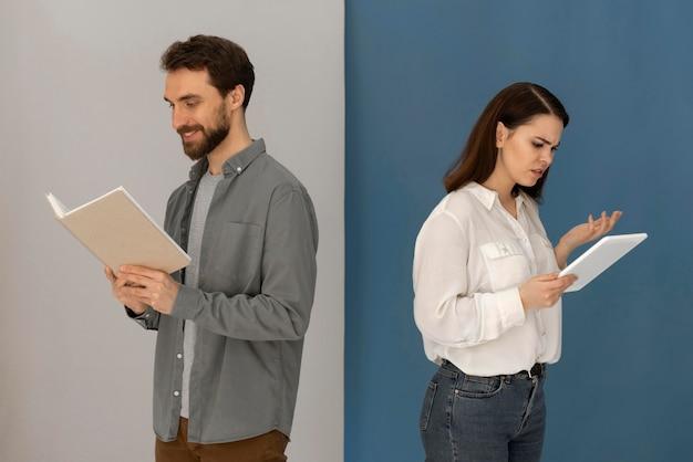 Costas com costas homem com livro e mulher com tablet