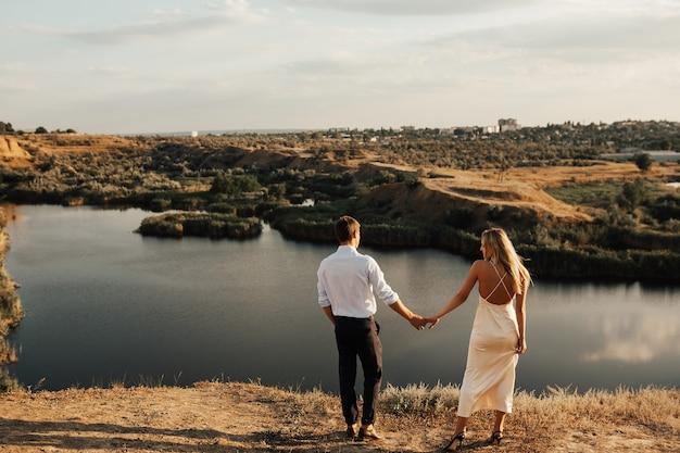 Costas da noiva e do noivo contra uma paisagem perfeita com rio e colinas.