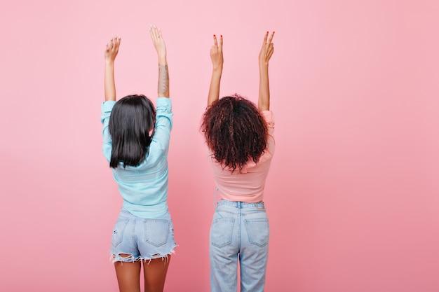 Costas de alongamento meninas morenas em jeans. glamourosas mulheres de cabelos escuros em trajes vintage, posando com as mãos ao alto.