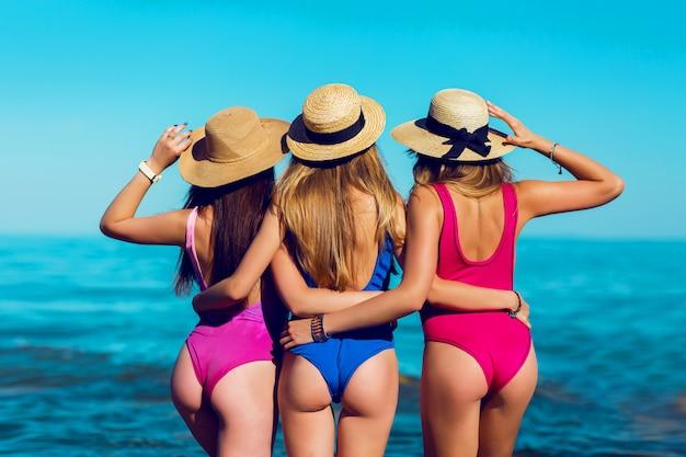 Costas de três mulheres com corpo perfeito em praia tropical em biquíni pequeno e estiloso.