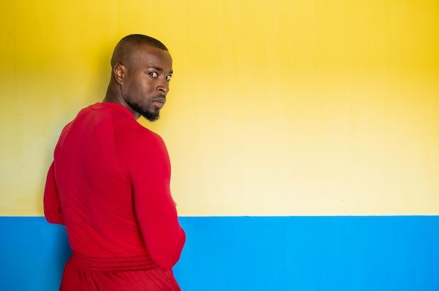 Costas de um homem africano esportivo com corpo perfeito em pé na frente de um fundo colorido girando a cabeça