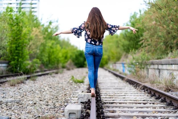 Costas de uma jovem mulher caminhando pelos trilhos do trem descalça e tentando manter o equilíbrio