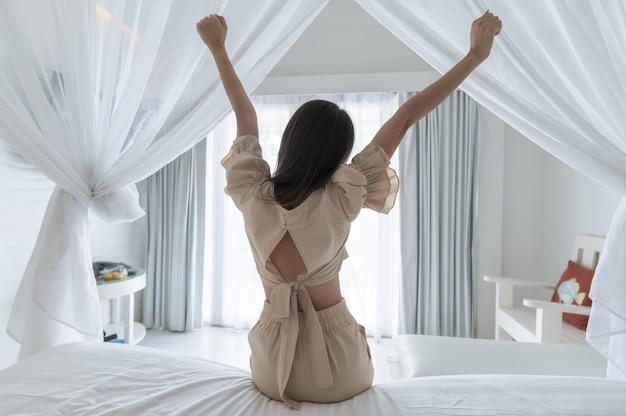 Costas de uma mulher asiática se espreguiçando depois de acordar no quarto branco com uma rede mosquiteira pela manhã