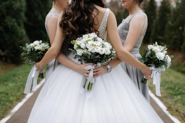 Costas de uma noiva e damas de honra com buquês de casamento eustoma brancos ao ar livre