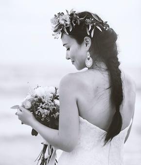 Costas de uma noiva segurando um buquê de flores