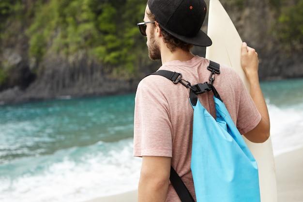 Costas do homem caucasiano com bolsa azul segurando a prancha, assistindo seus amigos surfando, montando ondas gigantes em dia de verão ventoso