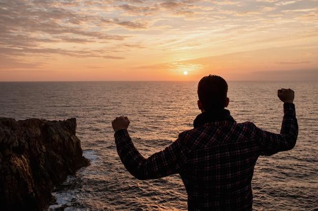 Costas do homem no topo de um penhasco rochoso contra o mar, olhando o pôr do sol, levantando os braços da vitória.