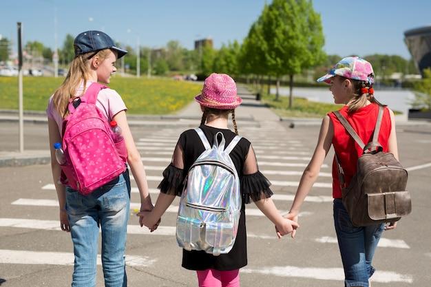Costas dos alunos com mochilas coloridas, movendo-se na rua