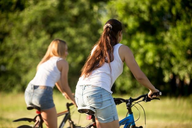 Costas duas meninas montam uma bicicleta