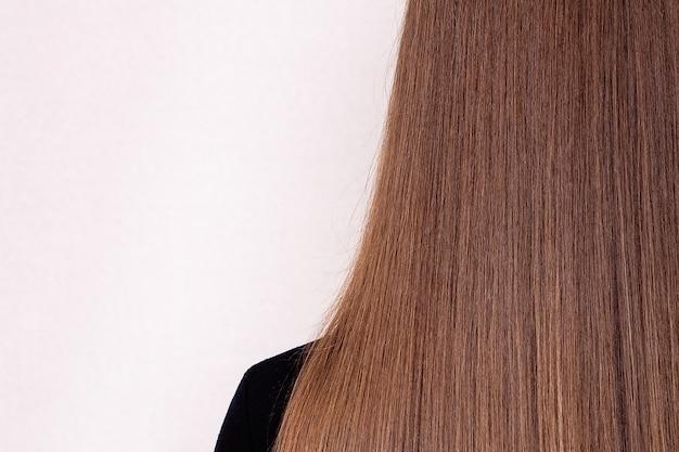 Costas femininas com cabelo castanho comprido natural em salão de cabeleireiro com espaço de cópia