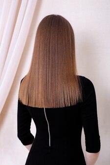 Costas femininas com cabelo castanho longo e reto e saudável em salão de cabeleireiro