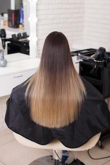 Costas femininas com cabelo castanho longo e reto em salão de cabeleireiro