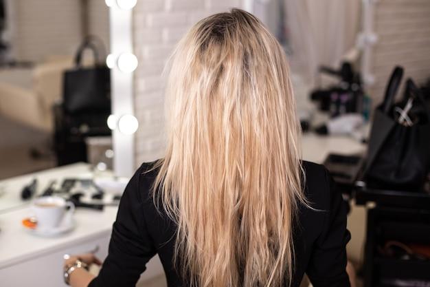 Costas femininas com cabelo loiro danificado