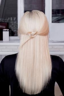 Costas femininas com cabelo loiro reto longo e saudável em salão de cabeleireiro
