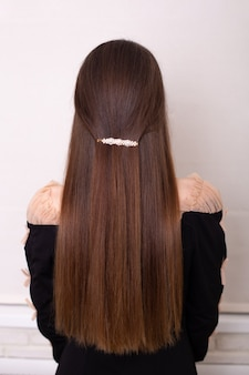 Costas femininas com cabelo longo e liso e castanho com presilha em salão de cabeleireiro