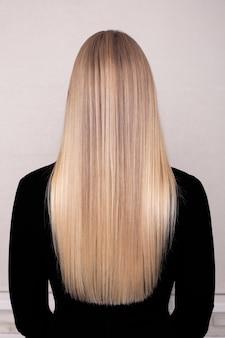 Costas femininas com cabelo louro comprido e reto em salão de cabeleireiro