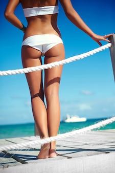 Costas glamour mulher bronzeada em lingerie branca em um píer