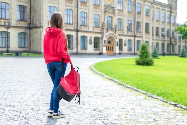 Costas traseiras atrás da foto em tamanho de corpo inteiro de triste chateado adolescente infeliz adolescente hippie usando tênis segurando descuidadamente sua bolsa escolar brilhante olhando para as portas