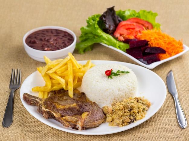Costela, arroz, feijão, batata e migalhas com acompanhamentos